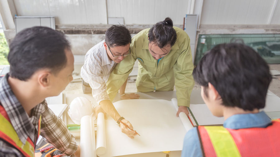 Group of architects making blueprint at construction site