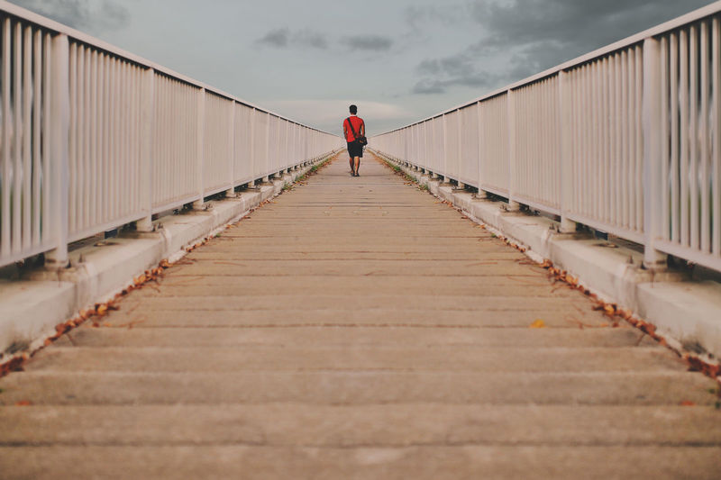 Rear View Of Man Walking On Footbridge Against Sky