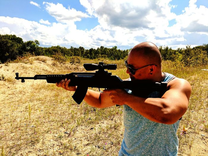 Man Shooting With Rifle On Field Against Sky