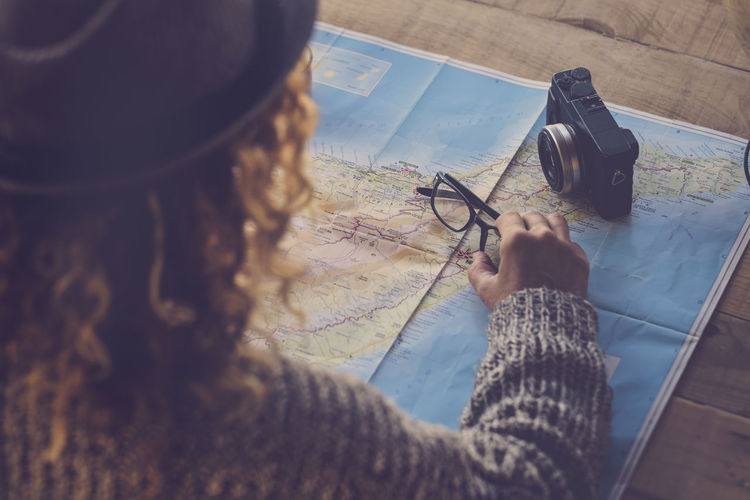 Hipster people, curly hair fantastic over the map planning a new travel. Real People One Person Holding Art And Craft Creativity High Angle View Lifestyles Activity Leisure Activity Drawing - Activity Indoors  Selective Focus Human Body Part Table Close-up Drawing - Art Product Women Paper Human Hand Skill  Hand Camera Fotography Eyeglasses  Studying Caucasian Casual Clothing Happiness Hat Dreaming