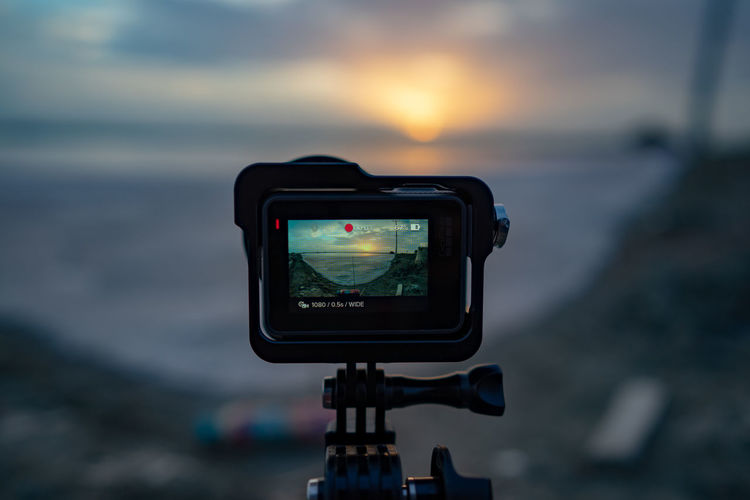 Close-Up Of Digital Camera Against Sea During Sunset