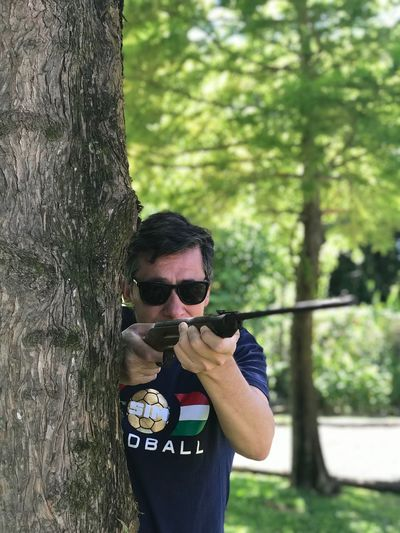 3...2...1...fire Hunter One Person Tree Real People Glasses Sunglasses Day Plant Leisure Activity Fashion Trunk Tree Trunk Young Adult Holding Lifestyles Nature Standing Casual Clothing Outdoors Young Men