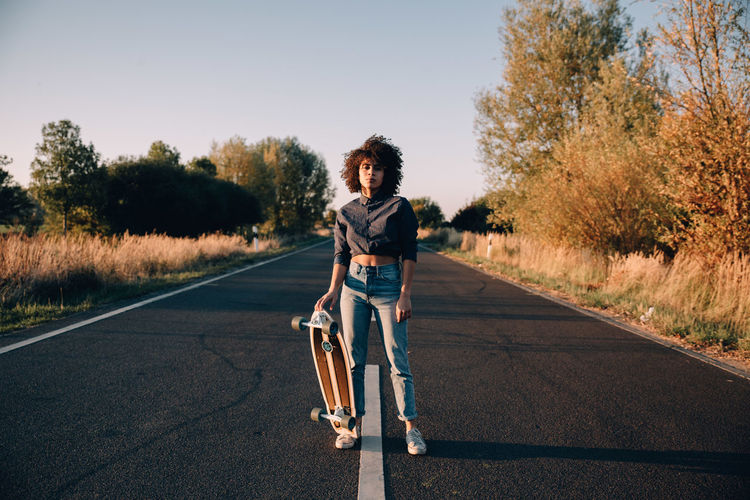Portrait of young woman holding skateboard while standing on road during sunset