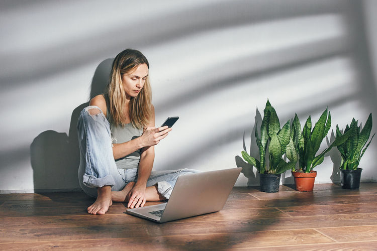 Woman using mobile phone while sitting on floor at home