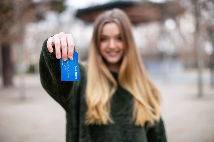 Portrait of woman holding credit card while standing in park
