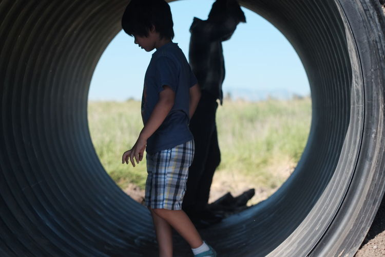 Side view of boys standing in tunnel at playground
