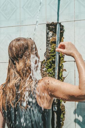 Water falling on woman in bathroom