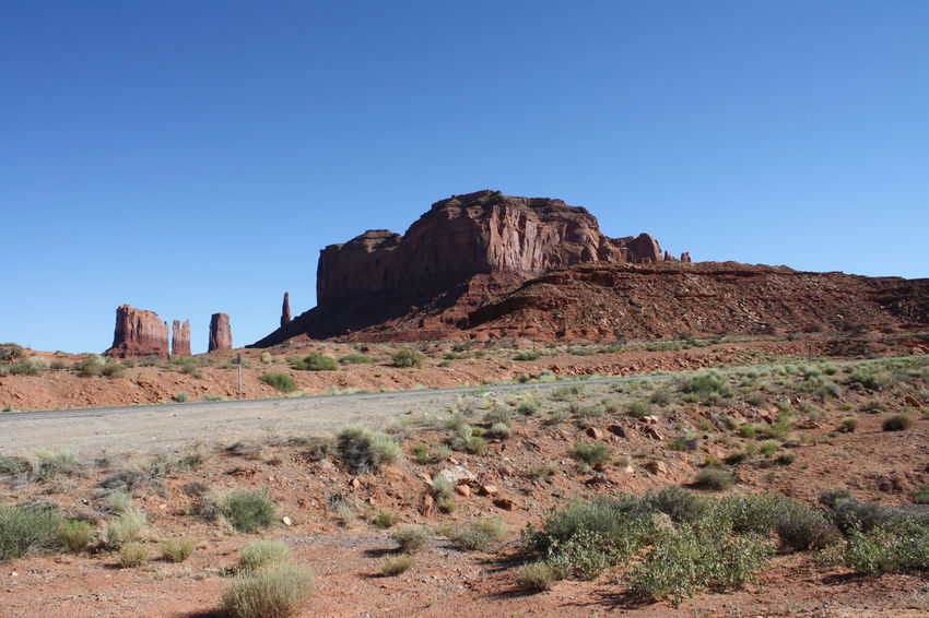 Monument Valley Monument Valley Tribal Park Monument Valley,Utah USA Arid Climate Beauty In Nature Blue Clear Sky Day Desert Landscape Nature No People Outdoors Plant Rock - Object Rock Formation Scenics Sky