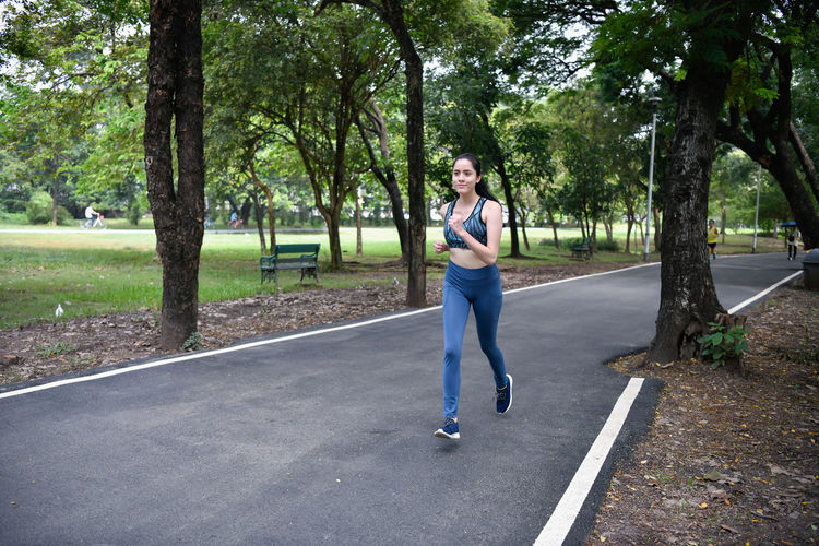 Full Length Of Woman Running On Road At Park
