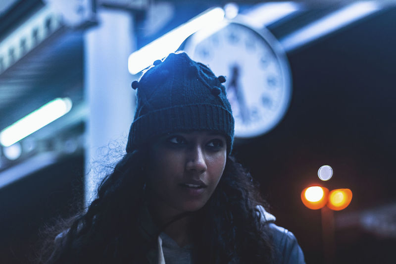 Close-Up Of Thoughtful Young Woman Standing At Railroad Station During Night
