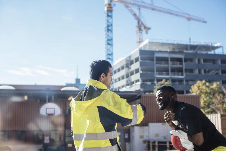 Men standing on construction site against sky