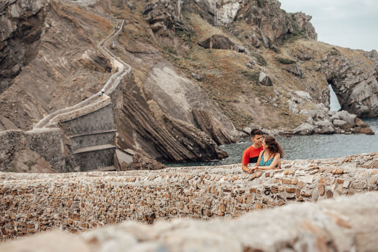 Couple romancing at beach against mountain