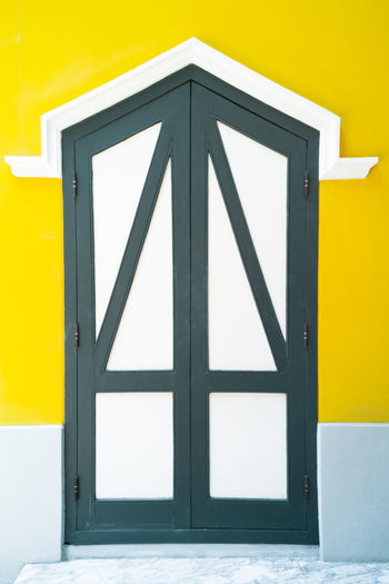 Architecture Black Color Building Building Exterior Built Structure Closedoor Communication Day Design Door Entrance Letter No People Outdoors Safety Shape Sign Single Object Triangle Shape Wall - Building Feature Yellow