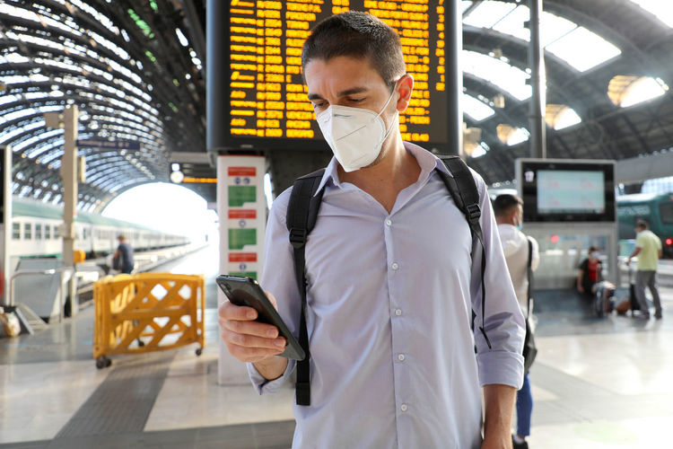 Man wearing mask and using mobile phone at airport