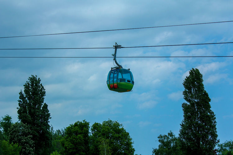 A Gondola Lift/ Cable car in the air Tree Cable Low Angle View Plant Sky Nature Cloud - Sky Hanging Green Color Day Cable Car Overhead Cable Car No People Transportation Growth Mode Of Transportation Connection Outdoors Electricity  Blue Cable Car Aerial Tramway Aerial Tram Gondola Lift