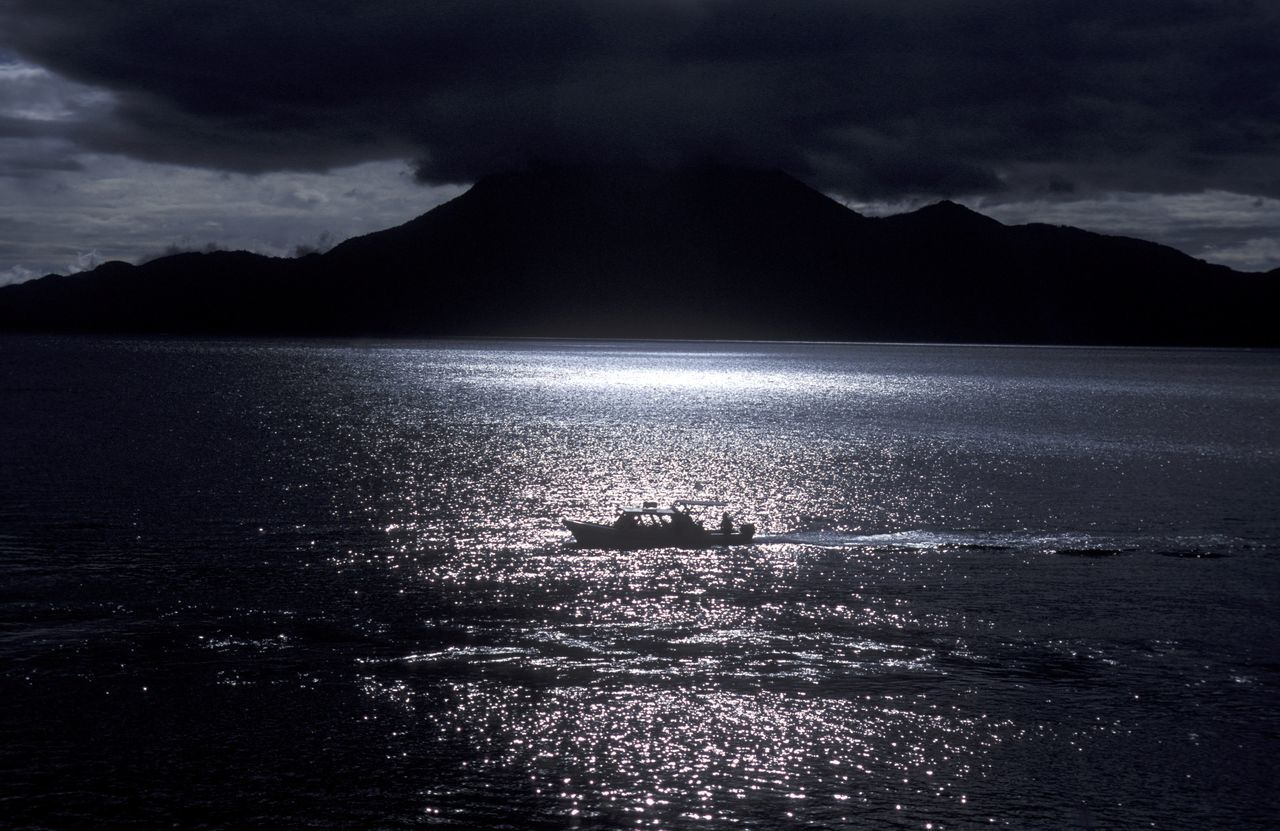 Mid Distance View Of Silhouette Boat Sailing In Sea At Dusk