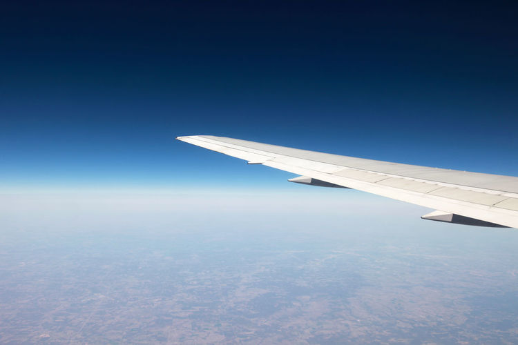 Aerial view of aircraft wing against clear blue sky