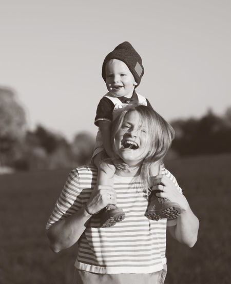 Happy mother carrying son on shoulders while standing in park