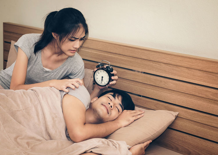 Woman Holding Alarm Clock By Men Sleeping On Bed At Home