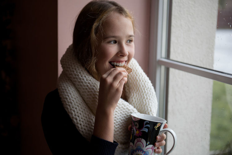 Teenage girl having coffee while sitting by window at home