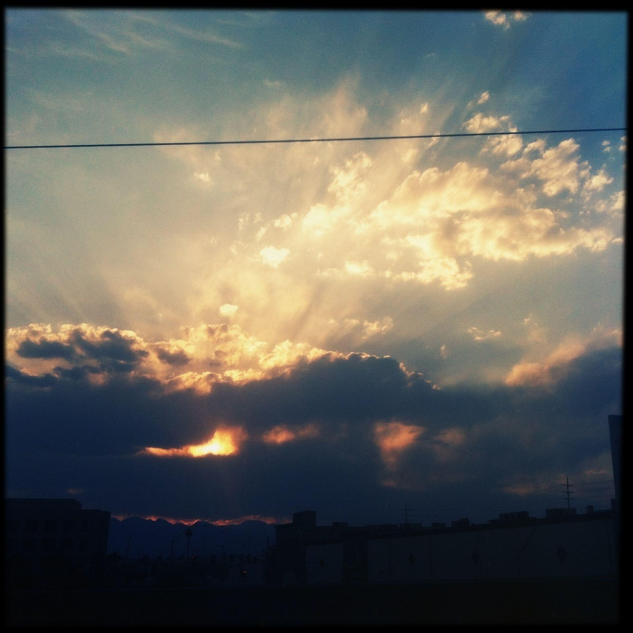 sunset, sky, silhouette, building exterior, cloud - sky, architecture, built structure, transfer print, cloud, power line, orange color, beauty in nature, city, auto post production filter, cloudy, nature, scenics, sunlight, electricity pylon, sun