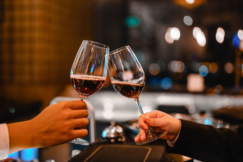 Cropped hands of man and woman toasting wine