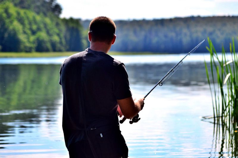 Rear view of man fishing at lake