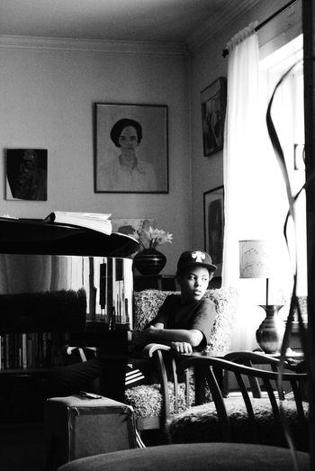 Teenage Boy Sitting On Armchair At Home