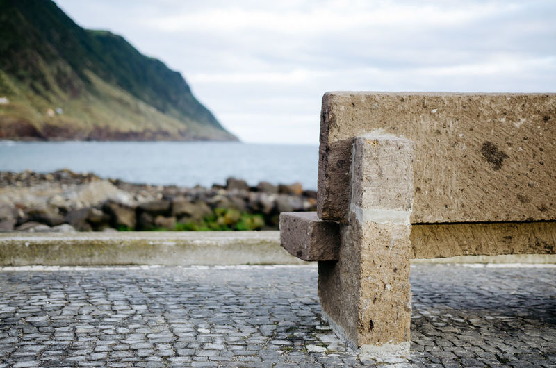 Empty stone bench by sea against sky