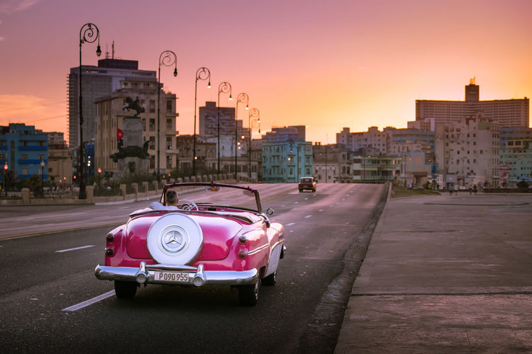 Cars on city street by buildings against sky during sunset