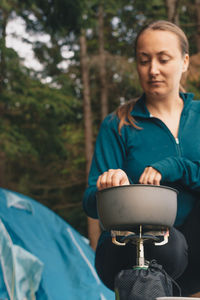 Woman cooking food outdoors Camping Cooking Cooking A Meal Meal Stove Woman Camp Stove Campstove Casual Clothing Close-up Cooking Pan Day Female Focus On Foreground Forest Front View Nature One Person Outdoors People Real People Sitting Tent Tree Young Adult Young Women Camp Food Stories