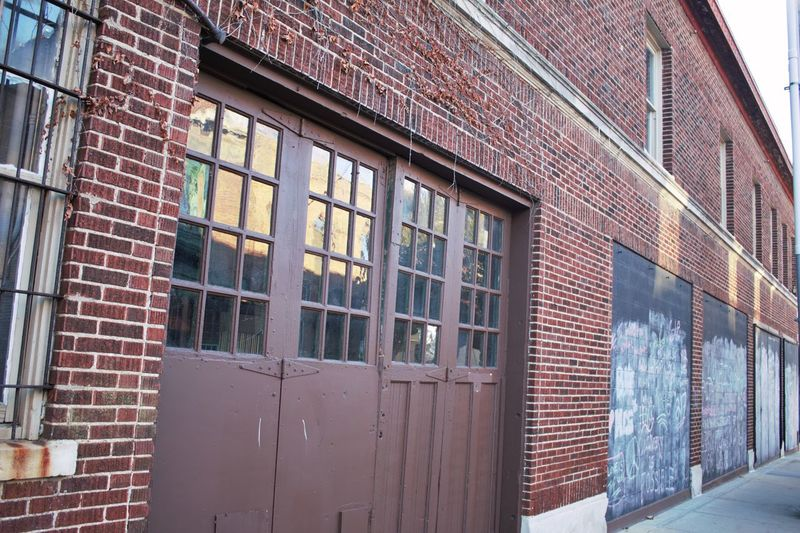 Lonely building with black board chalk walls for street drawing Alleyway Architecture Black Board Building Exterior Built Structure Chalk Art Chalkboard Day Large Doors No People Outdoors Red Brick Red Brick Wall Window