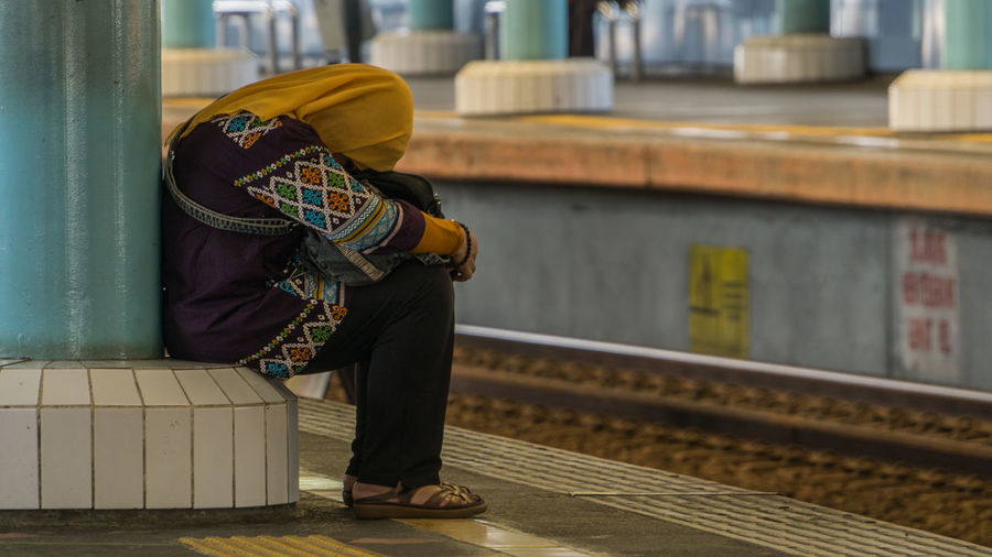 Side View Of Woman Sitting At Railroad Station Platform