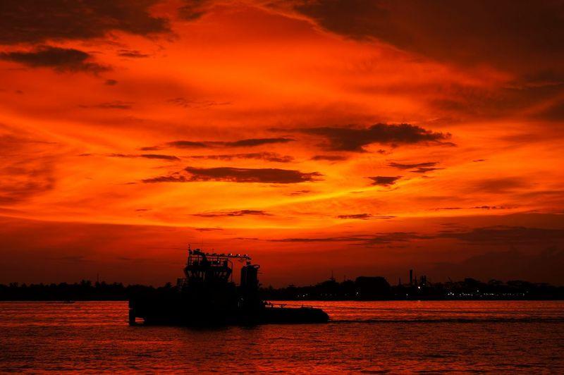 Silhouette Nautical Vessel Sailing On River Against Orange Sky