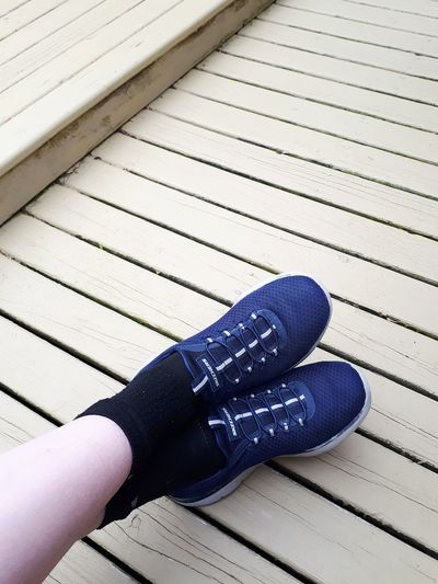 Low section of person wearing shoes on wood