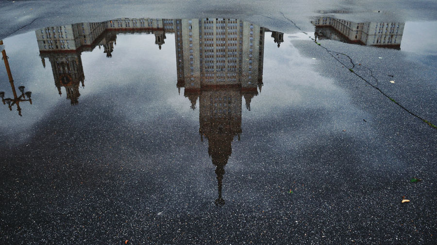High angle view of reflection of buildings in puddle