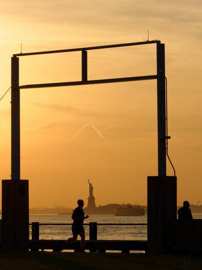 Silhouette man running by sea against sky during sunset