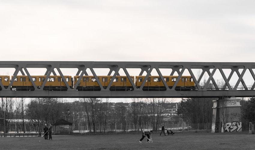 Train On Railway Bridge Above People On Playing Field