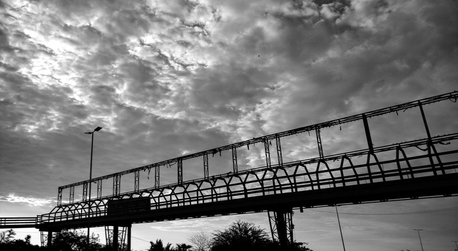 Silhouette Cloud - Sky Bridge - Man Made Structure Urban Exploration Urban Geometry Urbanstyle Street Light Urban Exploring Streetphotography Urban Landscape Black And White Photography Ansel Adams Inspired Film Noir Old-fashioned Bridge View Bridge Photography Connection Urban Lifestyle Isolated monochrome photography Low Angle View City Street