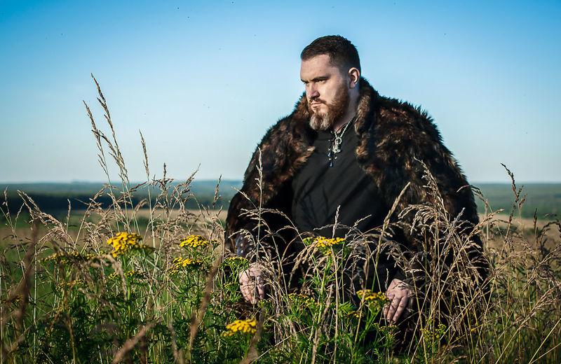 Hunter Standing On Grassy Field Against Sky