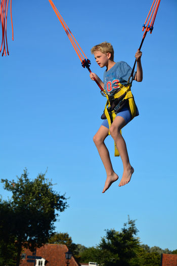 Low angle view of boy jumping against sky