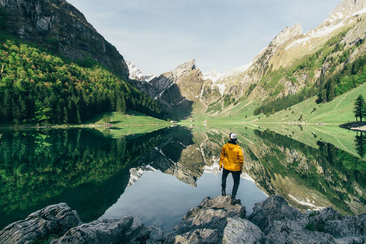 Rear View Of Man Looking At Seealpsee Lake By Mountains