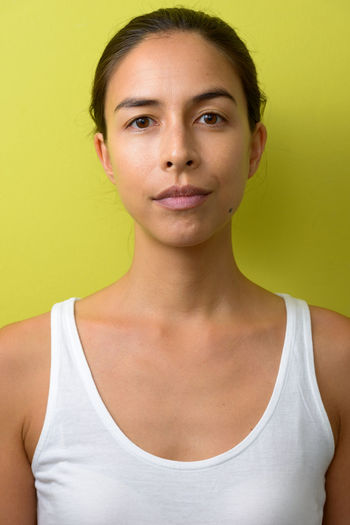 Portrait of beautiful young woman against yellow background