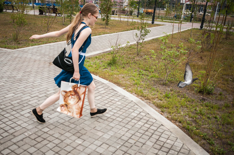 Side view of a teenage girl running outdoors