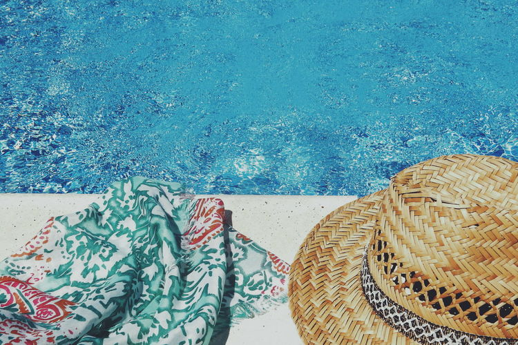 High angle view of scarf and hat by swimming pool during sunny day