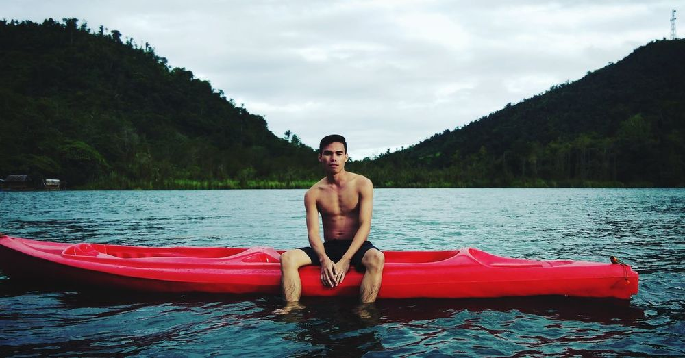 Portrait of shirtless man sitting in kayak on lake against mountains