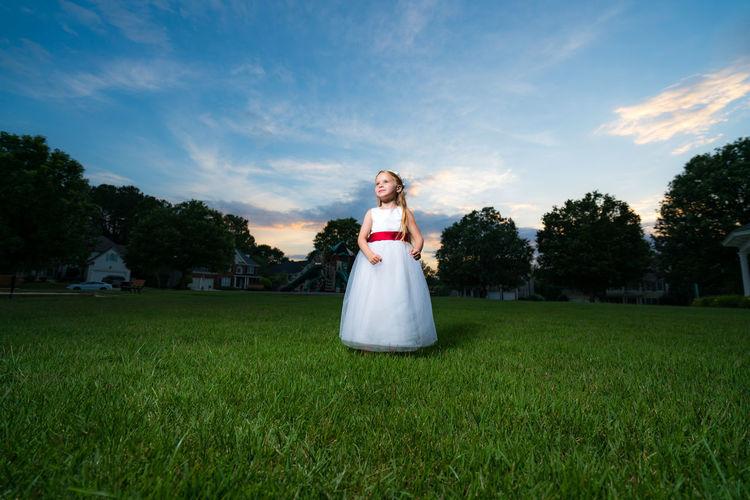 Cute flower girl in white dress standing on grassy field against sky during sunset