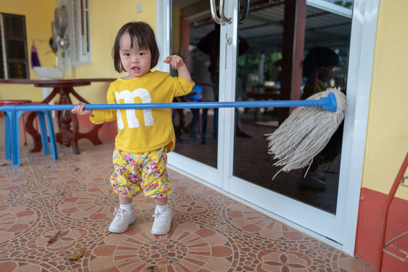 Portrait of cute baby girl moping floor at home