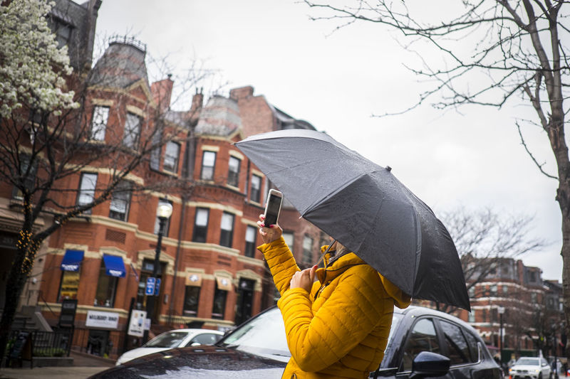 Side view of woman with umbrella using mobile phone in city
