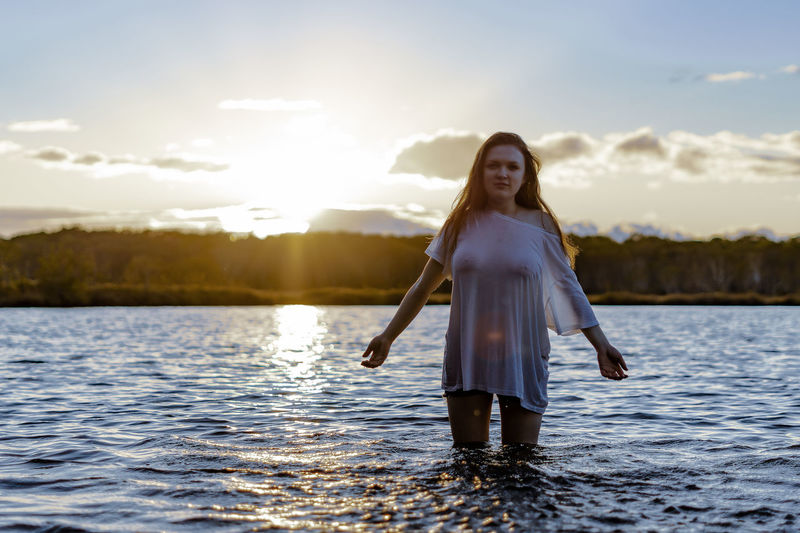 Adult Beautiful Woman Beauty In Nature Emotion Front View Hairstyle Happiness Lake Leisure Activity Looking At Camera Nature One Person Portrait Sky Smiling Standing Sunset Water Women Young Adult